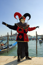 image of mardi-gras  - black and red jester in front of gondolas on grand canalveniceitaly welcomes you to carnivale the mardi gras of europe - JPG