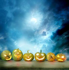 stock photo of halloween  - Spooky halloween pumpkins on a wooden table - JPG
