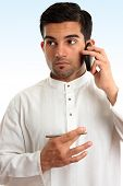 image of salwar  - Ethnic mixed race businessman wearing traditional robe is using a mobile phone and looking sideways - JPG