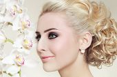 Close-up portrait of young beautiful blond girl with smoky eyes and stylish prom hairdo poster