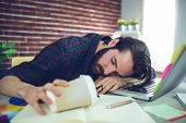 Tired editor holding disposable cup while sleeping on office desk poster