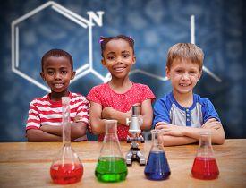 picture of beaker  - Cute pupils standing with arms crossed behind beaker against blue chalkboard - JPG
