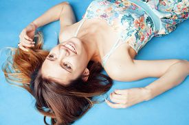 picture of fool  - young pretty woman fooling around on blue background close up smiling - JPG