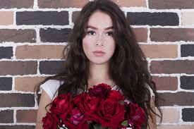 picture of curvy  - Portrait of young beautiful thoughtful girl with dark curvy hair with red roses bouquet near the brickwall - JPG