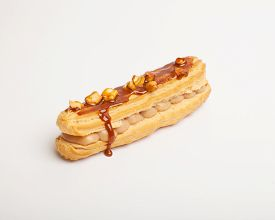 stock photo of eclairs  - An eclair with caramel and nuts on white background  - JPG
