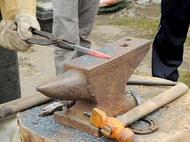 foto of anvil  - Smith handles the rod iron on the anvil - JPG