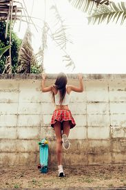 foto of mini-skirt  - Sporty young woman with sexy ass in a red tartan mini skirt with blue penny skateboard trying to climb over the fence of a tropical garden - JPG