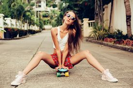 image of mini-skirt  - Skinny young lady in a sexy red tartan mini skirt sit on her blue penny skateboard longboard shortboard in the middle of the tropical street - JPG
