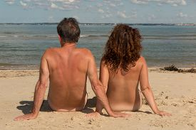 picture of naturist  - a Naked couple sitting on the beach - JPG