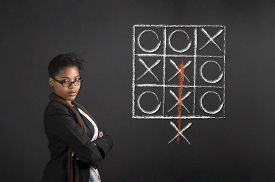 foto of tic  - South African or African American woman teacher or student with arms folded tic tac toe diagram on chalk black board background - JPG