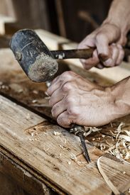 pic of chisel  - Closeup of a carpenter hands working with a chisel and hammer on wooden workbench - JPG