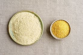 stock photo of millet  - Millet seeds and millet flour in small bowls - JPG