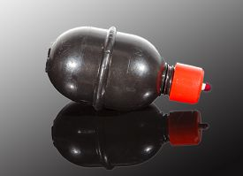 stock photo of grenades  - Paintball Grenade with paint On dark Reflective Surface - JPG