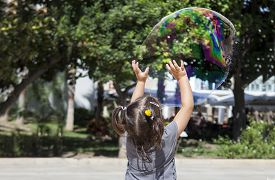 picture of hughes  - Three years old girl playing in the city with a huge bubble just before explode it