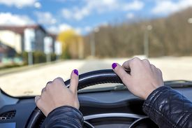 image of steers  - Hands of female driver on steering wheel Woman holds the passenger car steering wheel - JPG