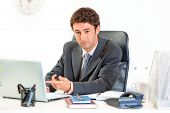 Modern business man sitting at office desk and pointing finger on laptop