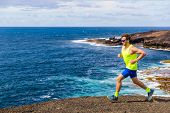 Trail runner athlete man ultra running on rocky trail path with ocean water nature landscape. Active poster