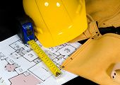 pic of construction industry  - Home construction items icluding a hard hat a leather tool belt a tape measure and floor plans - JPG