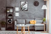 Black Clock Above Grey Settee poster