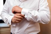 Man Buttons Cuff Link On Cuffs Sleeves Luxury White Shirt. Close Up Of Man Hand Wears White Shirt An poster