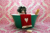 Dog Bath. A happy Shih Tzu dog ready to take a bath in the tub. He is wearing a shower cap and has a poster