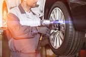 Midsection of male mechanic repairing cars wheel in workshop poster
