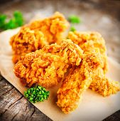 Fried chicken wings and legs on wooden table. Breaded Crispy fried kentucky chicken tasty dinner. Cl poster