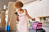 african american woman checking flight on smartphone at airport with luggage poster