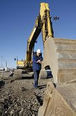 stock photo of jcb  - driver inspecting scoop on large digger - JPG