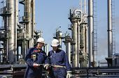 two engineers working in oil and gas industry, refinery in background