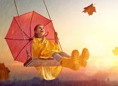 Happy funny child with red umbrella under the autumn shower. Girl is wearing yellow raincoat, rubber poster