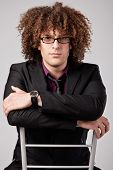 picture of black curly hair  - young curly man in suit sit on chair wearing eyeglasses - JPG