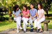 picture of asian woman  - Four Asian women sitting on a bench in a park and talking - JPG