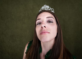 foto of spoiled brat  - Proud woman with tiara on green background - JPG