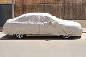 A Car Parked With Protective Cover Silver. Car Under A Protective Cover Parked In The Courtyard In S poster