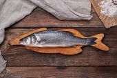 Fresh Whole Sea Bass Fish On Brown Cutting Board , Top View, Copy Space poster