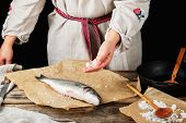 Fresh Whole Sea Bass Fish Lying On Brown Paper And A Chef Salt A Product, Black Background poster