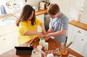 Young Downs Syndrome Couple Following Recipe On Digital Tablet To Bake Cake In Kitchen At Home poster