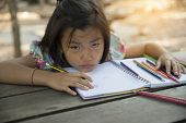 Cute Asian Girl Doing Homework,she Is Tired And Lazy ,do Not Want To Do Homework. poster
