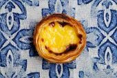 Egg Tart, Traditional Portuguese Dessert, Pastel De Nata. Blue Textile Background. Close Up. Top Vie poster