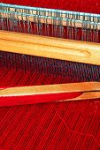stock photo of handloom  - Close up shot of loom with red thread - JPG