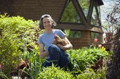 stock photo of hen house  - Woman at home with her chickens in her garden - JPG