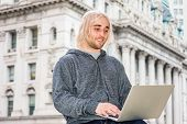 Man Working Outside. Young Hipster College Student With Long Blonde Hair, Wearing Gray Sweater With  poster