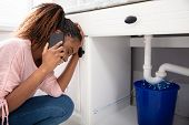 Young Woman Calling Plumber Crouching In Front Of Water Leaking From Sink Pipe poster
