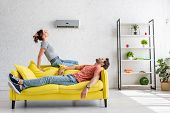 Young Man And Woman Resting On Yellow Sofa Under Air Conditioner At Home poster