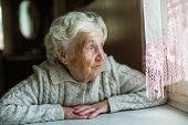 An elderly old woman looks sadly out the window. Care for lonely pensioners. poster