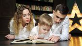 Happy Young Family Mom, Son And Dad Are Reading A Book Together Laying On The Floor At Home In Livin poster