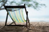 A Canvas Bed On White Sand And Sea Sky Background. On Vacation Relax Travel Sitting Canvas Chair On  poster