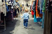 Cute Caucasian Blond Toddler Boy Walking Alone At Clothes Retail Store Between Rack With Hangers. Ba poster