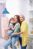 Beautiful Mature Woman With Daughter And Grandchild In Kitchen poster